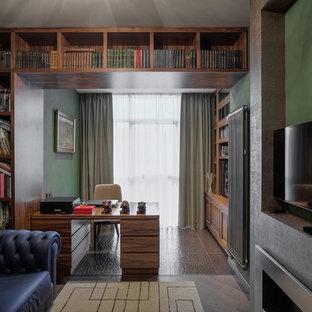Foto de despacho actual con paredes verdes, chimenea lineal, marco de chimenea de metal y escritorio independiente