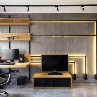На фото: рабочее место в стиле лофт с встроенным рабочим столом и серым полом с