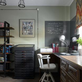 Inredning av ett industriellt hemmabibliotek, med gröna väggar, mörkt trägolv, ett fristående skrivbord och brunt golv
