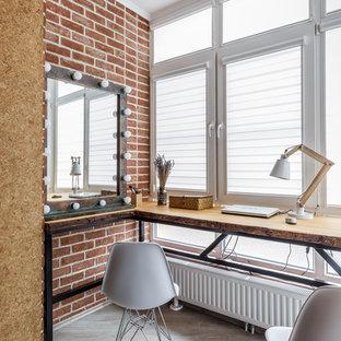 Idée de décoration pour un bureau bohème avec un mur rouge, un bureau indépendant et un sol gris.