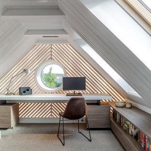 На фото: рабочее место среднего размера в современном стиле с ковровым покрытием, серым полом, встроенным рабочим столом и белыми стенами без камина