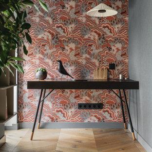 Cette photo montre un grand bureau tendance avec un mur bleu, un sol en bois brun, un bureau indépendant, un sol marron et du papier peint.