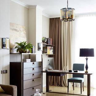 На фото: рабочее место в стиле неоклассика (современная классика) с белыми стенами, светлым паркетным полом, отдельно стоящим рабочим столом и бежевым полом
