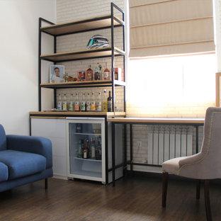他の地域の中サイズのコンテンポラリースタイルのおしゃれなホームオフィス・仕事部屋 (マルチカラーの壁、ラミネートの床、自立型机、茶色い床) の写真