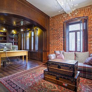 Aménagement d'un bureau industriel avec un mur marron, un sol en bois foncé et un bureau indépendant.