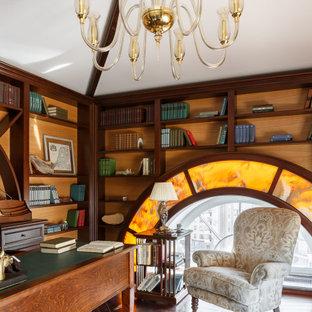 На фото: кабинет в классическом стиле с темным паркетным полом, отдельно стоящим рабочим столом и коричневым полом с