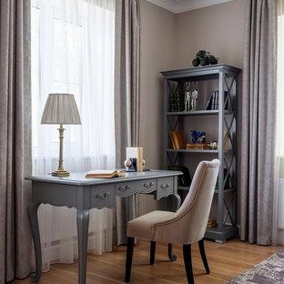 Идея дизайна: рабочее место в классическом стиле с бежевыми стенами, паркетным полом среднего тона и отдельно стоящим рабочим столом