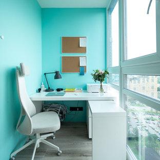 Свежая идея для дизайна: кабинет среднего размера в современном стиле с синими стенами, отдельно стоящим рабочим столом и серым полом - отличное фото интерьера