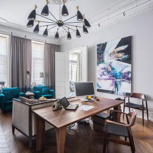 Неиссякаемый источник вдохновения для домашнего уюта: рабочее место среднего размера в стиле фьюжн с серыми стенами, паркетным полом среднего тона, отдельно стоящим рабочим столом и коричневым полом