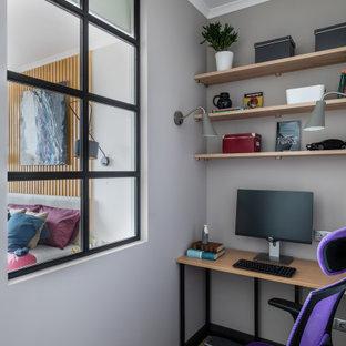 На фото: маленькое рабочее место в скандинавском стиле с серыми стенами, отдельно стоящим рабочим столом и бежевым полом с