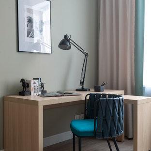 Свежая идея для дизайна: рабочее место в современном стиле с полом из ламината, отдельно стоящим рабочим столом, серыми стенами и бежевым полом - отличное фото интерьера