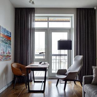 Идея дизайна: рабочее место в современном стиле с белыми стенами, паркетным полом среднего тона, отдельно стоящим рабочим столом и коричневым полом