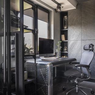 Пример оригинального дизайна: рабочее место в стиле лофт с серыми стенами, темным паркетным полом и отдельно стоящим рабочим столом