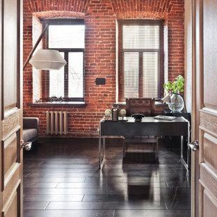 Inredning av ett industriellt stort hemmabibliotek, med röda väggar, mörkt trägolv, ett fristående skrivbord och brunt golv