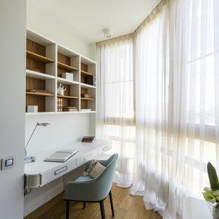 Klassisches Arbeitszimmer ohne Kamin mit Arbeitsplatz, weißer Wandfarbe, braunem Holzboden und Einbau-Schreibtisch in Moskau