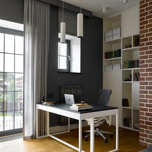 Стильный дизайн: рабочее место среднего размера в современном стиле с серыми стенами, паркетным полом среднего тона, отдельно стоящим рабочим столом и коричневым полом - последний тренд
