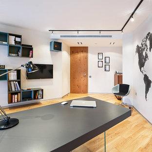 На фото: рабочее место среднего размера в современном стиле с белыми стенами, паркетным полом среднего тона и отдельно стоящим рабочим столом с