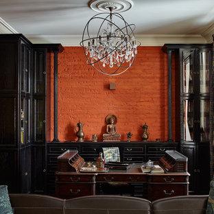 Ejemplo de despacho ecléctico con paredes rojas y escritorio independiente