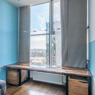 モスクワの広いコンテンポラリースタイルのおしゃれな書斎 (青い壁、ラミネートの床、暖炉なし、自立型机、茶色い床) の写真