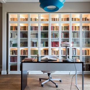 Идея дизайна: кабинет в современном стиле с серыми стенами, паркетным полом среднего тона, отдельно стоящим рабочим столом и коричневым полом