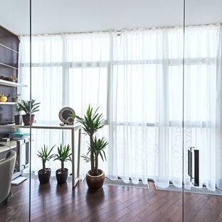 Modelo de despacho clásico, grande, con paredes blancas, suelo de madera en tonos medios, chimeneas suspendidas, marco de chimenea de piedra y suelo marrón