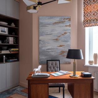 На фото: кабинет в стиле современная классика с розовыми стенами, паркетным полом среднего тона, отдельно стоящим рабочим столом и коричневым полом