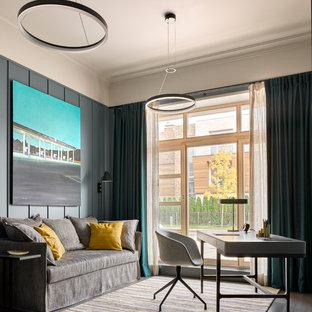 На фото: рабочее место в скандинавском стиле с серыми стенами, темным паркетным полом, отдельно стоящим рабочим столом и коричневым полом