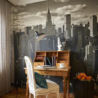 Exempel på ett klassiskt hemmabibliotek, med mellanmörkt trägolv, ett fristående skrivbord och orange golv