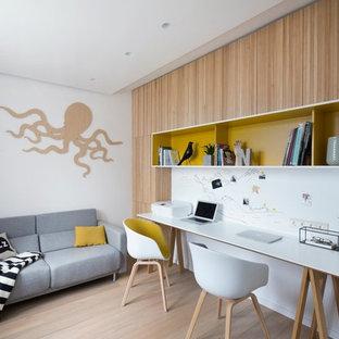 Неиссякаемый источник вдохновения для домашнего уюта: рабочее место в современном стиле с белыми стенами, паркетным полом среднего тона, отдельно стоящим рабочим столом и коричневым полом без камина