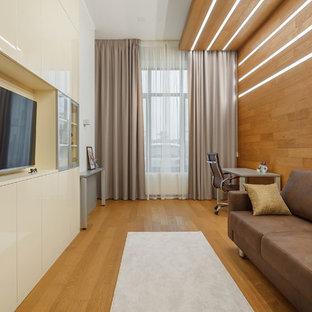 На фото: рабочее место в современном стиле с коричневыми стенами, паркетным полом среднего тона, отдельно стоящим рабочим столом и коричневым полом с