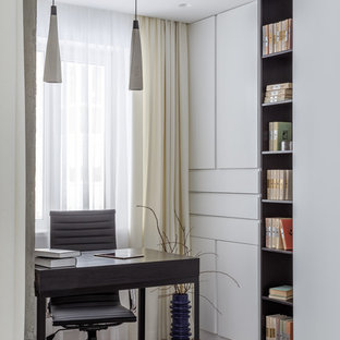Inspiration for a contemporary study in Other with white walls, light hardwood flooring, a freestanding desk and beige floors.