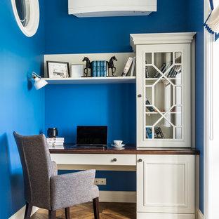 Ejemplo de despacho casetón y papel pintado, clásico renovado, de tamaño medio, papel pintado, sin chimenea, con paredes azules, suelo de madera oscura, escritorio independiente, suelo marrón y papel pintado