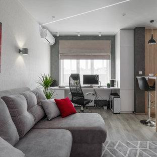 На фото: рабочее место среднего размера в современном стиле с белыми стенами, светлым паркетным полом, отдельно стоящим рабочим столом и серым полом