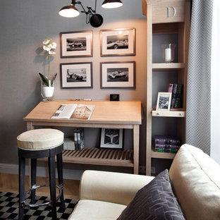 Klassisches Arbeitszimmer mit Studio, grauer Wandfarbe, freistehendem Schreibtisch und hellem Holzboden in Moskau