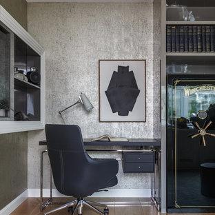 На фото: рабочее место среднего размера в современном стиле с паркетным полом среднего тона, отдельно стоящим рабочим столом, коричневым полом и серыми стенами с