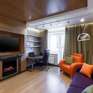 Idee per un ufficio contemporaneo di medie dimensioni con pareti verdi, pavimento in bambù, camino classico, cornice del camino in legno, scrivania autoportante e pavimento marrone