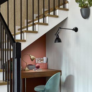 Kleines Modernes Arbeitszimmer ohne Kamin mit Arbeitsplatz, Einbau-Schreibtisch, braunem Holzboden und rosa Wandfarbe in Moskau