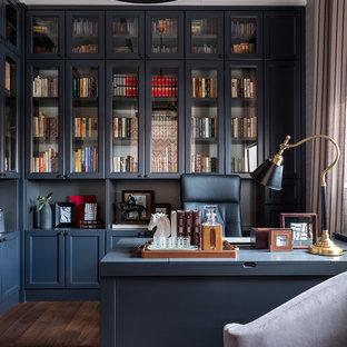 Ispirazione per uno studio tradizionale di medie dimensioni con libreria, pareti grigie, pavimento in legno massello medio, nessun camino, scrivania autoportante e pavimento marrone