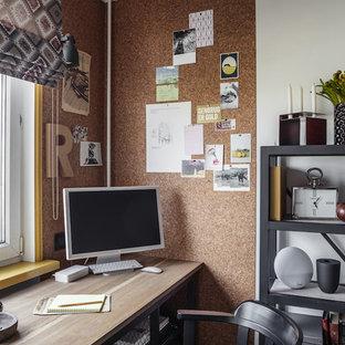 На фото: маленькое рабочее место в современном стиле с белыми стенами и отдельно стоящим рабочим столом с