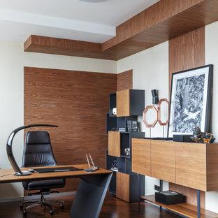 На фото: кабинет в современном стиле с белыми стенами, темным паркетным полом, отдельно стоящим рабочим столом и коричневым полом с