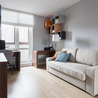 Foto de estudio contemporáneo, de tamaño medio, con paredes grises, suelo de madera clara, escritorio independiente y suelo turquesa