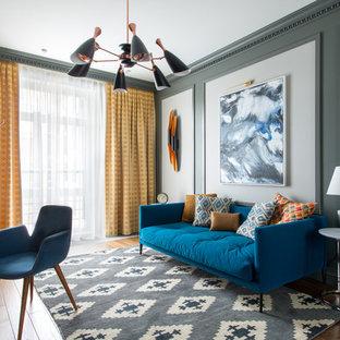 Свежая идея для дизайна: рабочее место в стиле современная классика с серыми стенами, паркетным полом среднего тона, отдельно стоящим рабочим столом и коричневым полом - отличное фото интерьера