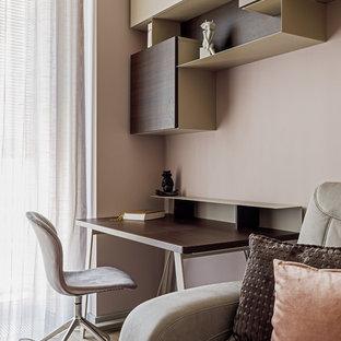 Неиссякаемый источник вдохновения для домашнего уюта: рабочее место среднего размера в современном стиле с светлым паркетным полом, бежевым полом, отдельно стоящим рабочим столом и розовыми стенами