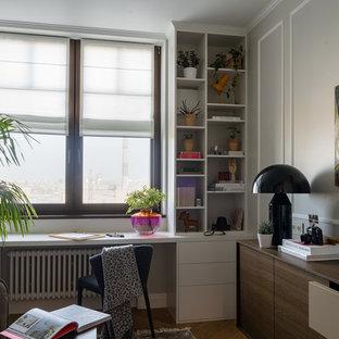 Свежая идея для дизайна: кабинет в современном стиле с серыми стенами, паркетным полом среднего тона, встроенным рабочим столом и коричневым полом - отличное фото интерьера