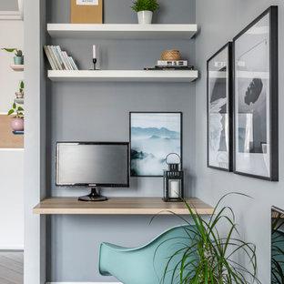Ejemplo de despacho escandinavo con paredes grises, suelo de madera en tonos medios, escritorio empotrado y suelo marrón