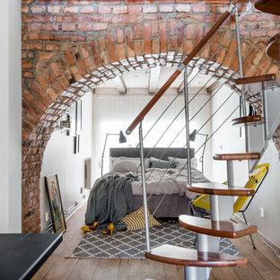 Cette image montre un petit sous-sol nordique avec un mur blanc, un sol en bois brun et aucune cheminée.
