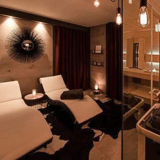Réalisation d'un sous-sol design donnant sur l'extérieur et de taille moyenne avec un mur noir, un sol en carrelage de céramique et un sol beige.