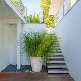 Idee per una grande taverna minimal con sbocco, pareti bianche, pavimento in legno verniciato e pavimento marrone