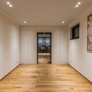 Idee per una taverna shabby-chic style interrata di medie dimensioni con pareti bianche, pavimento in legno massello medio e pavimento marrone