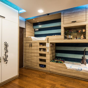 Small contemporary gender neutral teen's room in Mumbai with white walls, brown floors and medium hardwood flooring.